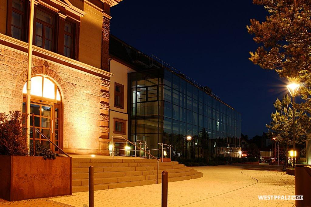 Blick auf den Haupteingang des Forum Alte Post in Pirmasens aus Nordosten bei Nacht.