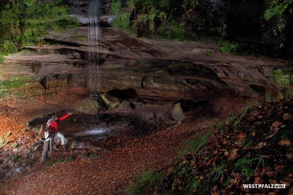 Innenansicht der Bärenhöhle mit Wasserfall des Höhlenbaches bei Rodalben. Gut zu erkennen ist die Schichtung des Sandsteins (2013).