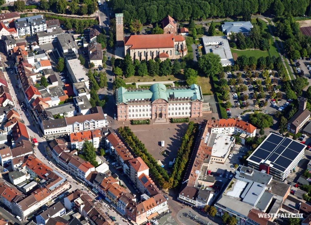 Luftaufnahme des Zweibrücker Schlosses mit vorgelagertem Schlossplatz von Süden. Im Hintergrund ist die Heilig-Kreuz-Kirche zu sehen. Am oberen Bildrand verläuft der Schwarzbach mit beidseitiger Baumallee.