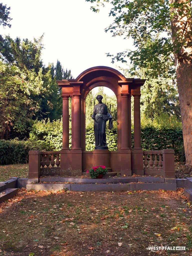 Grabstätte der Familie Brunck im Schlossgarten des Barockschlosses in Kirchheimbolanden. Zwischen mehreren Sandsteinsäulen steht auf einem Podest eine Bronzeplastik unter einem Bogen aus Sandstein.