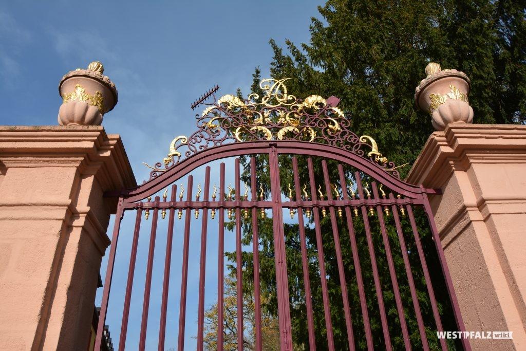 Schmiedeeisernes Tor zum Schlossgarten des Barockschlosses in Kirchheimbolanden. Über allem schwebt der Name des Fürsten Carl August, der die Glanzzeit begründete. Einer seiner beiden Anfangsbuchstaben taucht immer wieder spiegelverkehr auf, je nachdem von welcher Seite man aus die Sache betrachtet (2015).