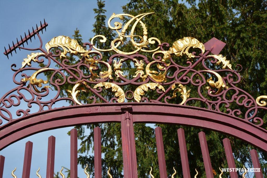 Schmiedeeiserner Gitteraufsatz des Tores zum Schlossgarten des Barockschlosses in Kirchheimbolanden. Es enthält die Initialien des Fürsten Carl August von Nassau-Weilburg (2015).