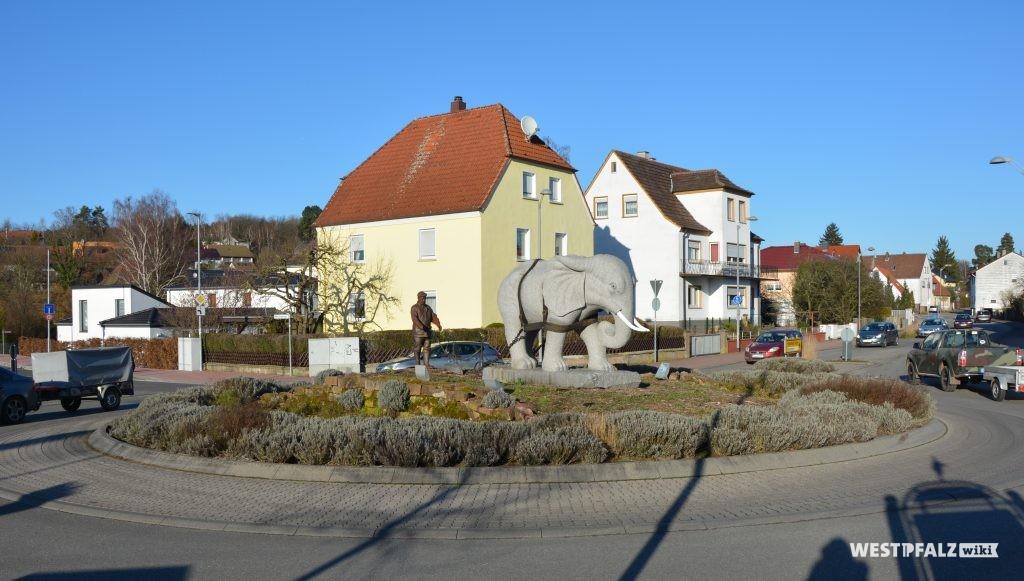 Granitskulptur eines Elefanten vor einem Pflug auf dem Verkehrskreisel in der Rosenhofstraße in Enkenbach.