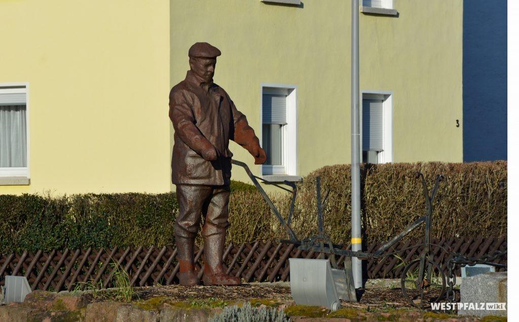 Der Schreinermeister Schmitt aus Gusseisen geformt, am Pflug hinter dem steinernen Elefanten in Enkenbach.