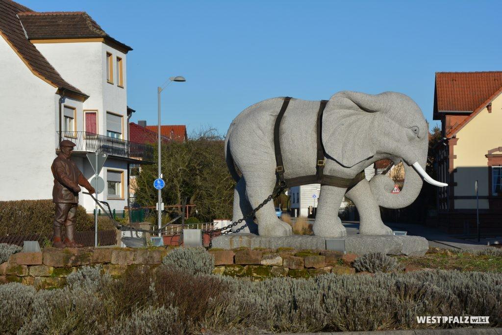 Die Granitskulptur eines Elefanten in einem Geschirr; dahinter befindet sich der Schreinermeister Schmitt aus Enkenbach.