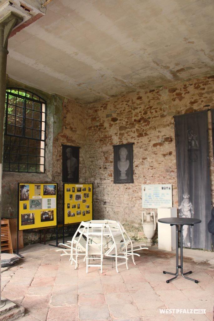 Innenraum der Orangerie mit ausgestelltem Informationsmaterial und einer Stuhlgruppe im Landschaftspark Gienanth.