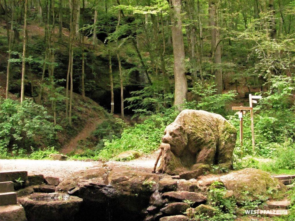 Im Vordergrund eine Bärenskulptur und ein steinernes Becken, in das Felsquellwasser aus der Bärenfelshöhle fließt. Im Hintergrund die Bärenfelshöhle (2014).