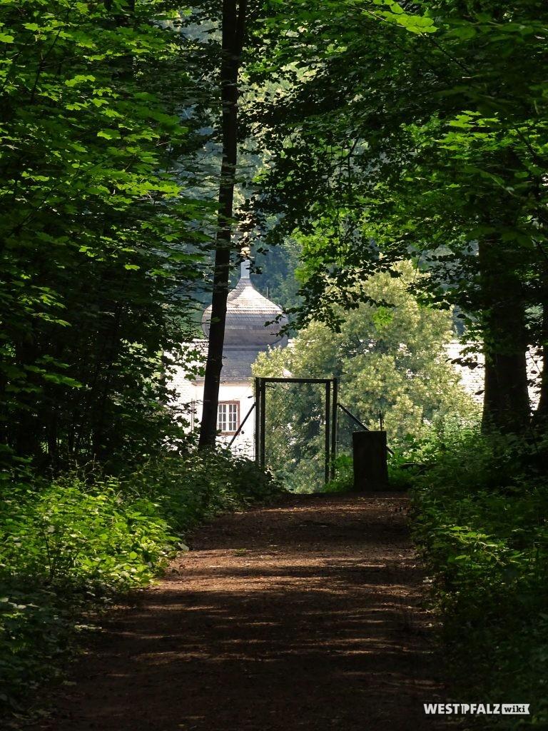 Weg durch den Wildrosengarten in Zweibrücken. Im Hintergrund ist das Landschloss Hotel Fasanerie zu sehen.