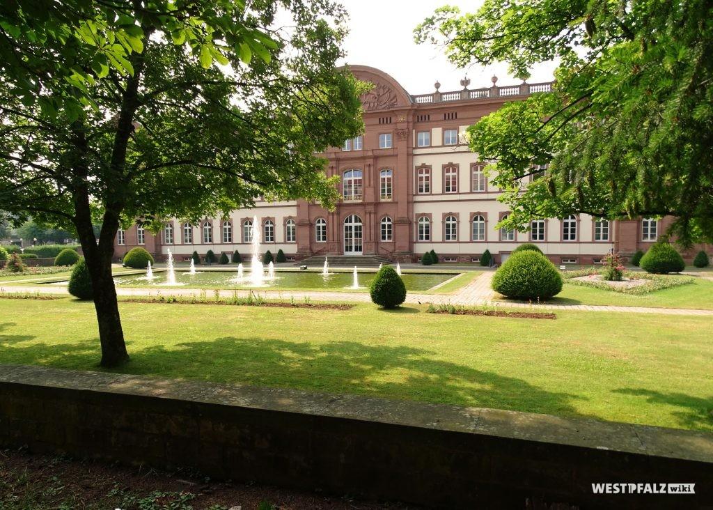 Bick über die niedrige Schlossmauer hinweg in den Garten des Zweibrücker Herzogschlosses. Vor dem Schlosseingang liegt ein rechteckiger Teich mit Wasserfontänen.