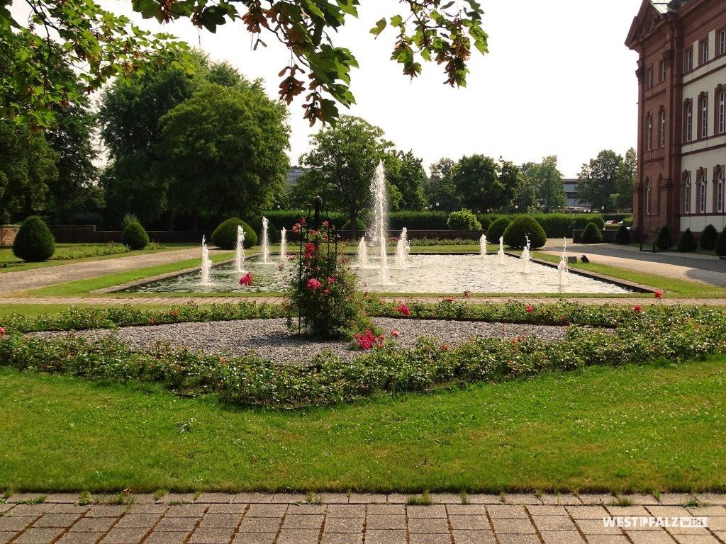 Gartenanlage des Zweibrücker Herzogschlosses. Ein Wegenetz, Bliumenbeete sowie ein rechteckiger Teich mit Wasserfontänen schmücken den Garten.
