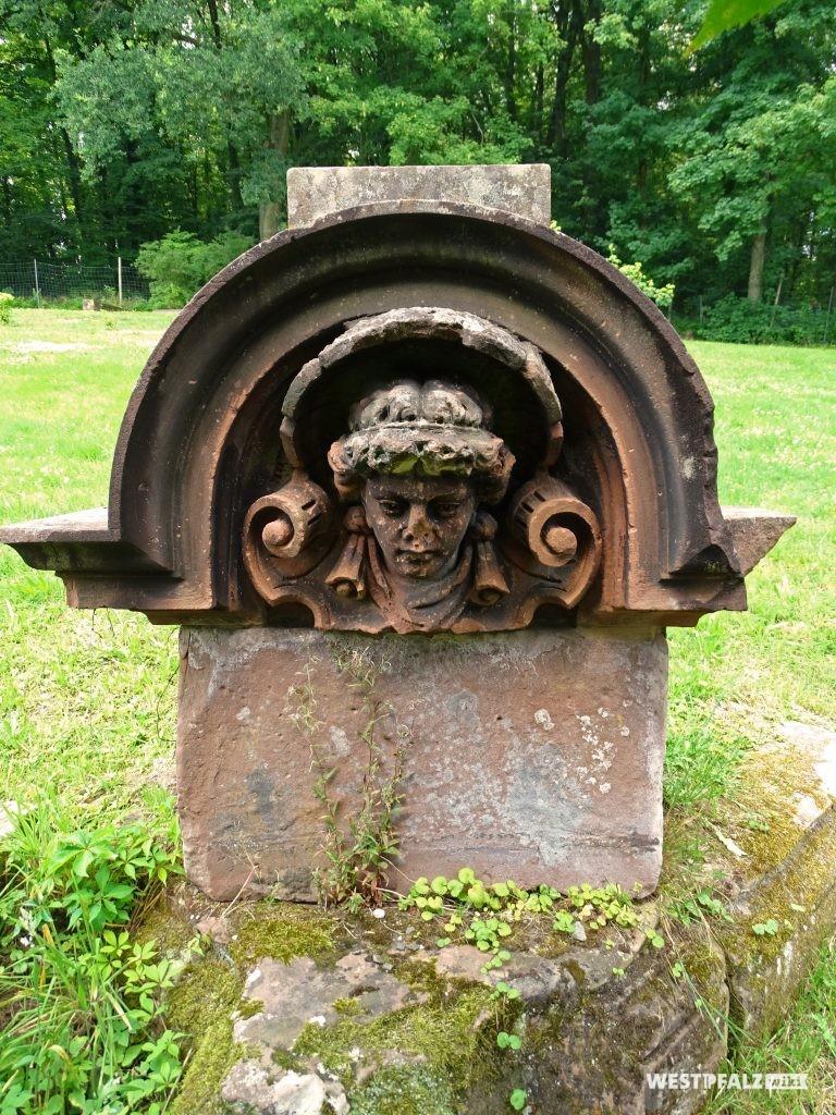 Sandsteinblock, vermutlich ein Kapitell mit einem in den Stein gemeißelten Menschenkopf unter einem Rundbogen.