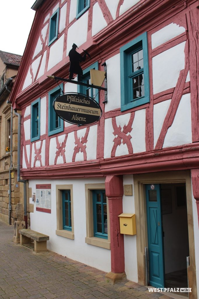 Fassade des Steinhauermuseums in Alsenz mit blauer Eingangstür und einem eisernen Schild darüber.