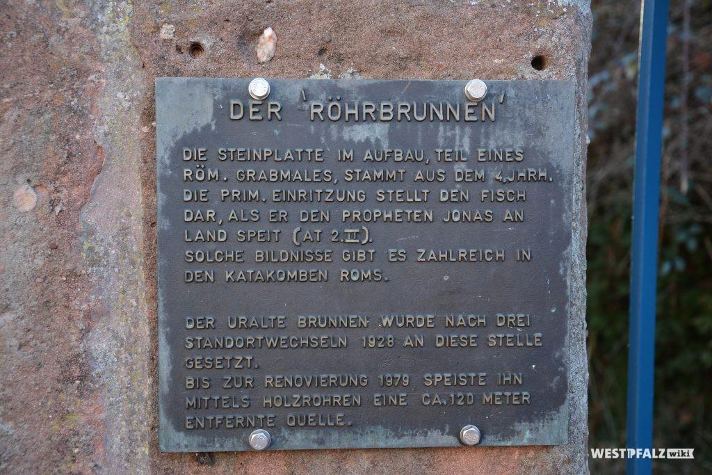 Eine eiserne Infotafel ist am Röhrbrunnen angebracht.