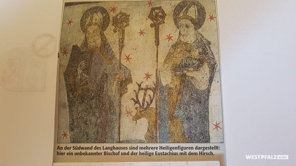 Innenbereich Simultankirche Oberndorf: An der Südwand des Langhauses sind mehrere Heiligenfiguren dargestellt. Hier ein unbekannter Bischof und der heilige Eustachius mit dem Hirsch.