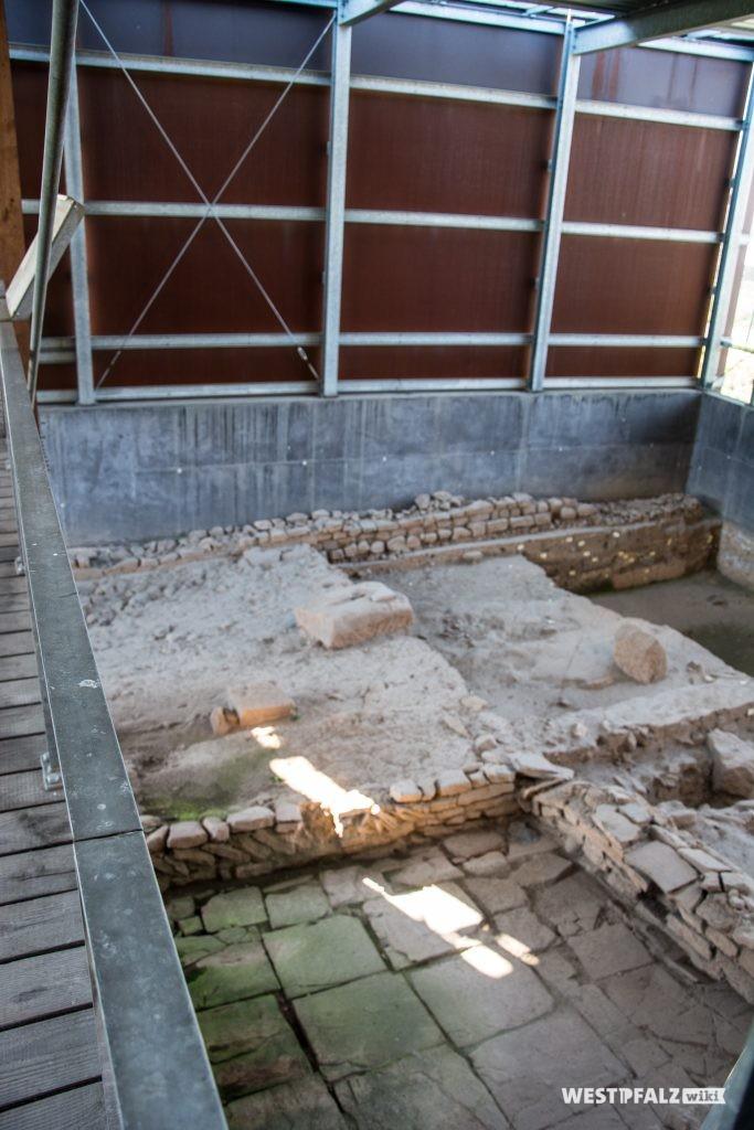 Von einer abgeschlossenen Halle überdachte Ausgrabungsstätte. Zu sehen ist ein Teil eines römischen Platzes