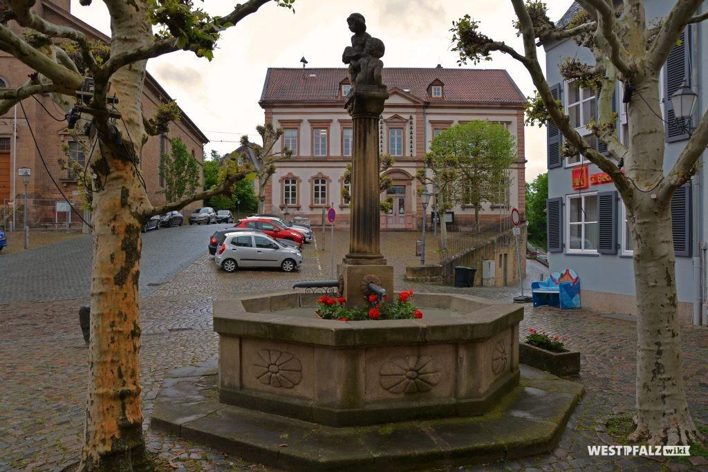 Hutmacherbrunnen am Marktplatz in Kusel. Im Hintergrund ist das Rathaus zu sehen
