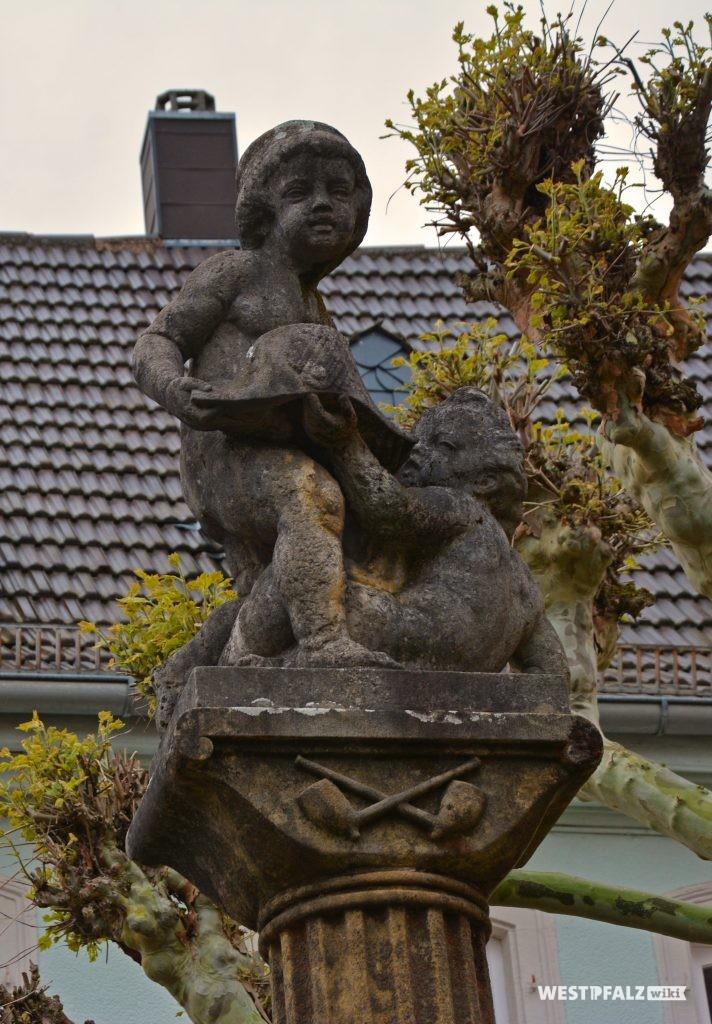 Figuren auf der Säule des Hutmacherbrunnens in Kusel. Zu sehen sind zwei spielende Kinder mit einem Schiffshut in den Händen