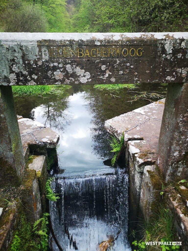Wasserauslauf am Absperrbauwerk mit Sandsteinfassung, in dem die Inschrift des gleichnamigen Rittersteins integriert ist