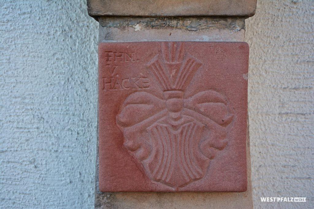In eine Tafel aus rotem Sandstein gehauenes Wappen der Freiherren von Hacke mit Inschrift