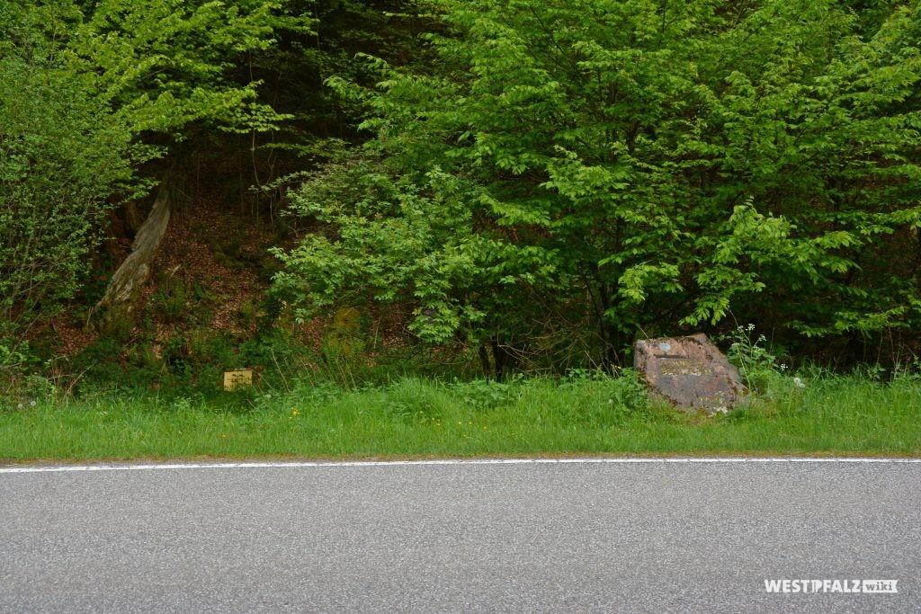 Ritterstein Nr. 153 am Straßenrand. Links hinter dem Ritterstein befindet sich das Naturdenkmal Hungerbrunnen
