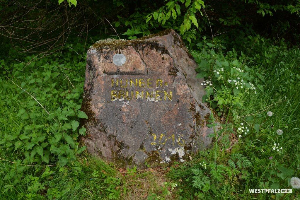 """Ritterstein Nr. 153 bei Kaiserslautern mit der Inschrift """"Hungerbrunnen"""" und """"PWV."""" (Pfälzerwald-Verein)."""