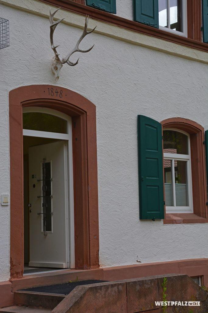 Eingangstür auf der Ostseite des Forstamtsgebäudes. In den Türsturz ist das Erbauungsjahr 1848 eingemeißelt. Darüber hängt der Schädel mit Geweih eines Hirsches