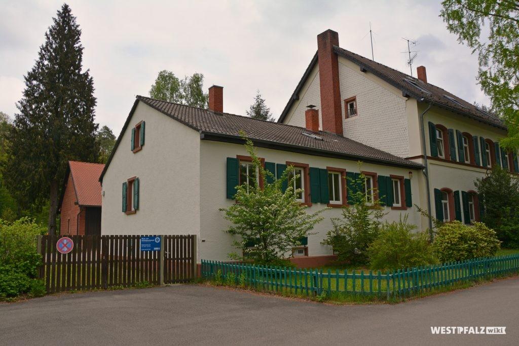 Blick von Westen auf ein Nebengebäude des Forstamts im Stiftswald. Dahinter befindet sich ein weiteres Gebäude aus Sandstein