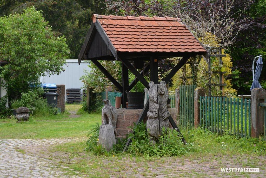 Brunnen mit einer hölzernen und mit Ziegel gedeckten Überdachung östlich des Forstamtsgebäudes. Davor stehen aus Holz geschnitzte Tierfiguren