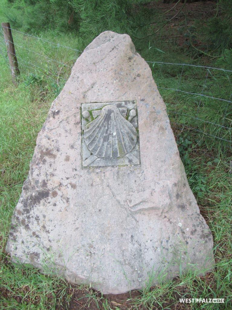 Fels mit dem Muschel-Symbol des Jakobpilgerwegs