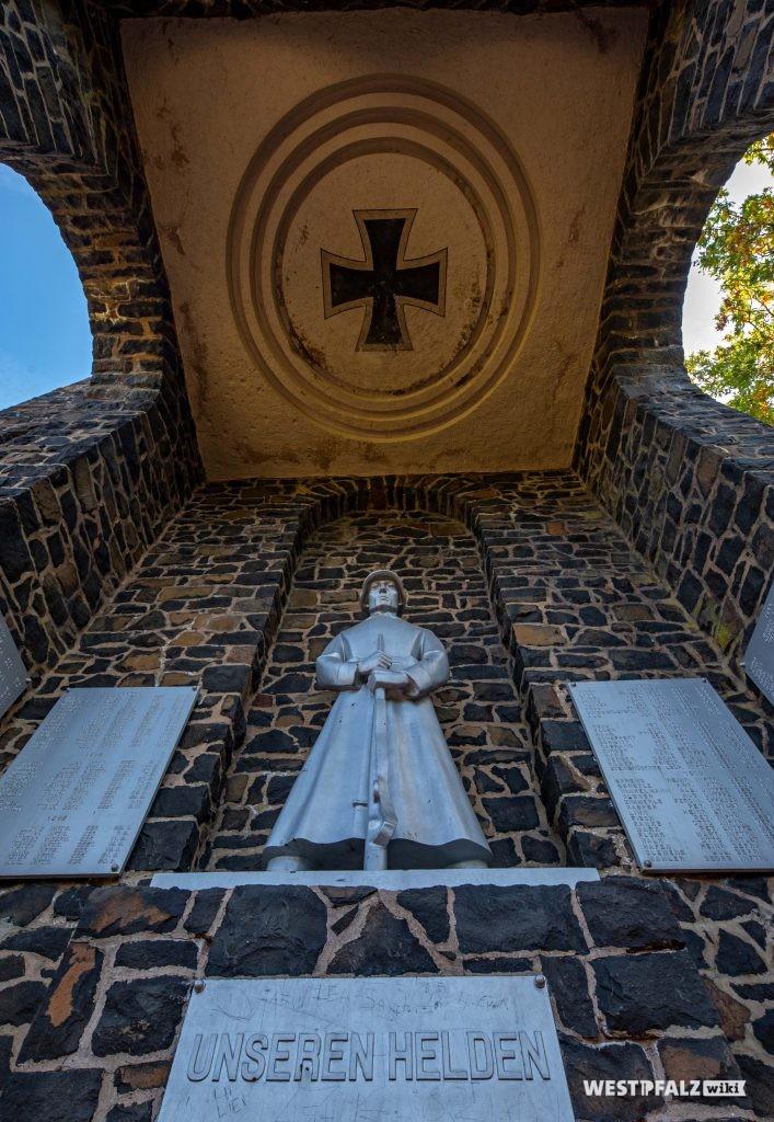 """Der """"Innenraum"""" des Kriegerdenkmals. An der Wand ist eine große Figur eines Soldaten angebracht. Rechts und links daneben je zwei Gedenktafeln. An der Decke ist das Symbol des """"Eisernen Kreuzes"""" zu sehen"""
