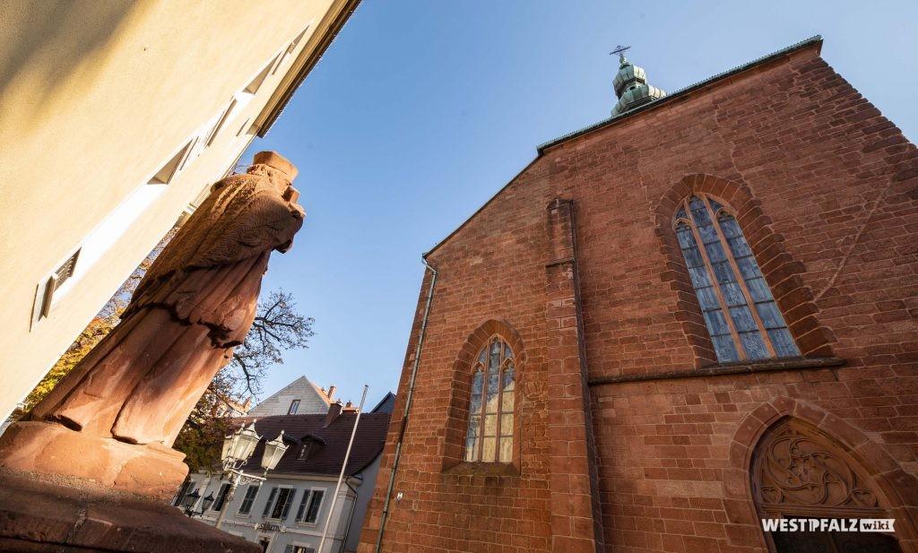 Blick auf die Portalseite im Westen. Links im Bild und außerhalb der Kirche steht eine Figur aus Sandstein mit einer Bibel in den Händen auf einem Sockel