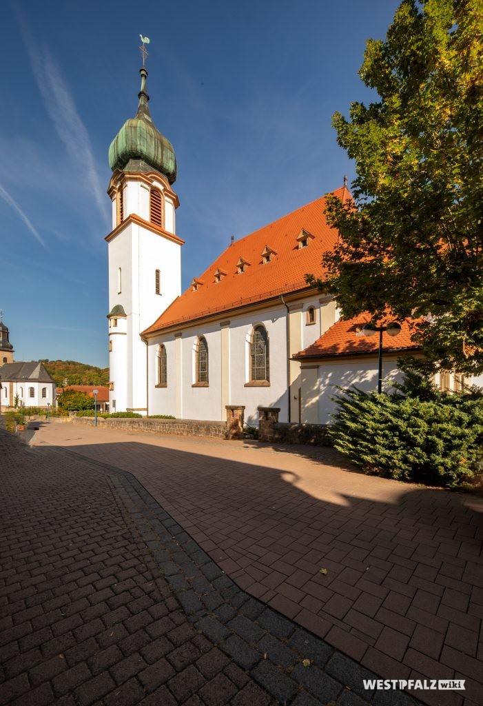 Blick auf das Langhaus und den Kirchturm der katholischen Kirche. Im Hintergrund ist die protestantische Kirche zu sehen