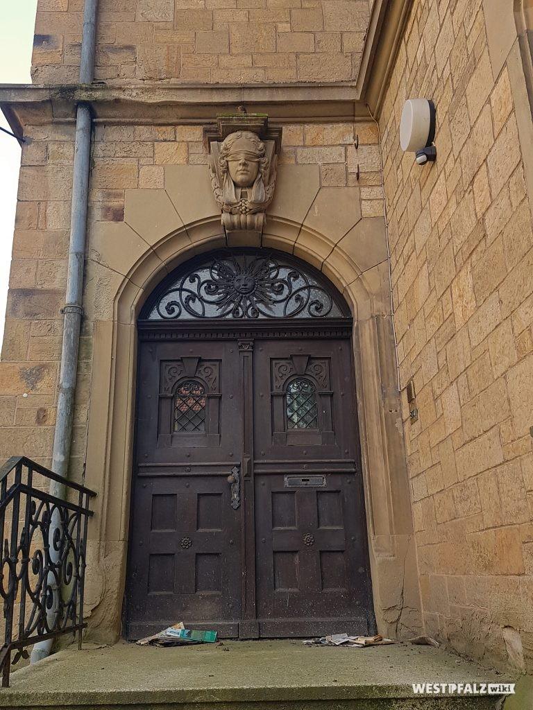 Eingangstür aus Holz mit der Figur der Justitia mittig über der Tür des ehemaligen Amtsgerichts in Obermoschel