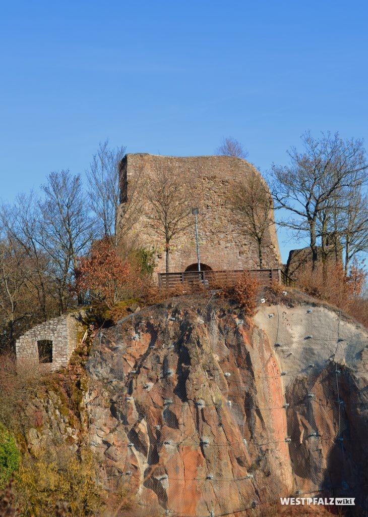 Blick in Richtung Westen auf eine steile Felswand. Oberhalb befinden sich die Reste der Bruchsteinschildmauer der Michelsburg