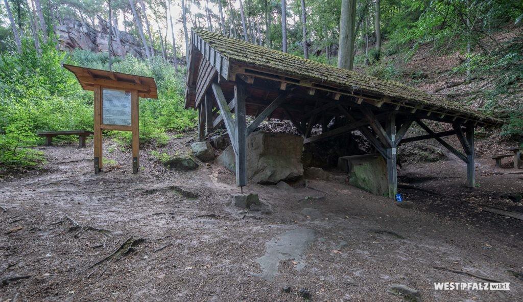Die beiden Heidenfelsen, überdacht von einer kleinen Hütte. Daneben eine Informationstafel