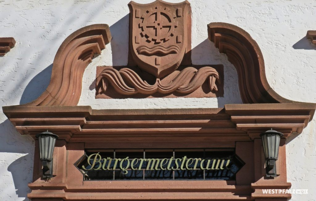 Ortswappen mit Sandsteinfries über der Eingangstür des Rathauses in Erfenbach