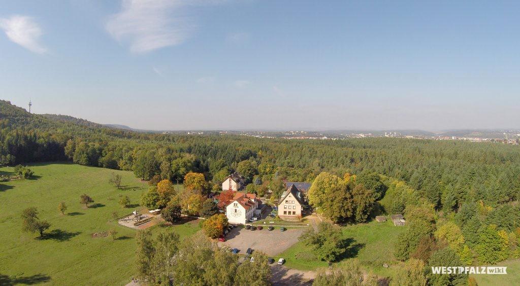 Luftaufnahme des Bremerhofs von Süden. Am Horizont ist die Stadt Kaiserslautern zu sehen