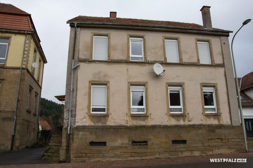 Frontansicht des alten Schulhauses. Am linken Bildrand das neue Schulhaus