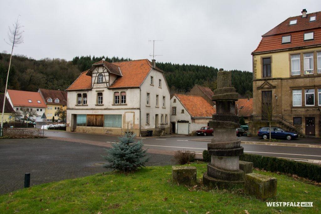 Ehemaliges Gast- und Warenhaus Cappel in Hinzweiler. Im Vordergrund der Dorfplatz mit Brunnen