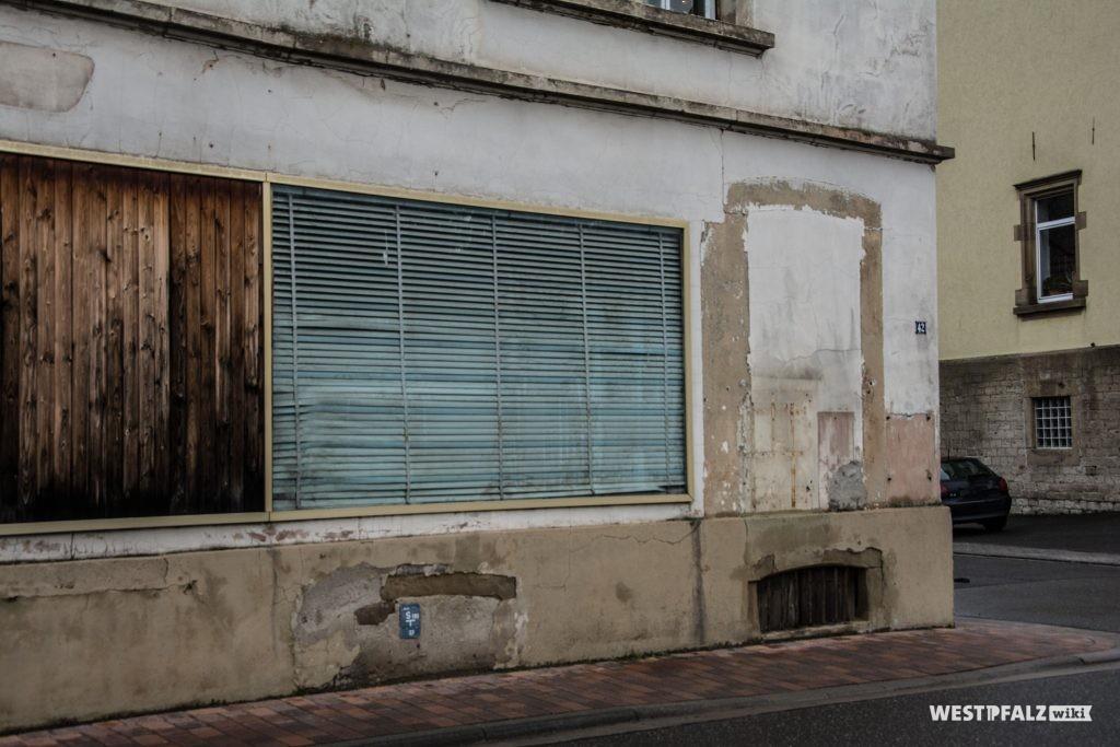 Schaufenster des ehemaligen Gast- und Warenhauses Cappel. Neben dem Schaufenster ist ein zugemauertes bodentiefes Fenster zu erkennen