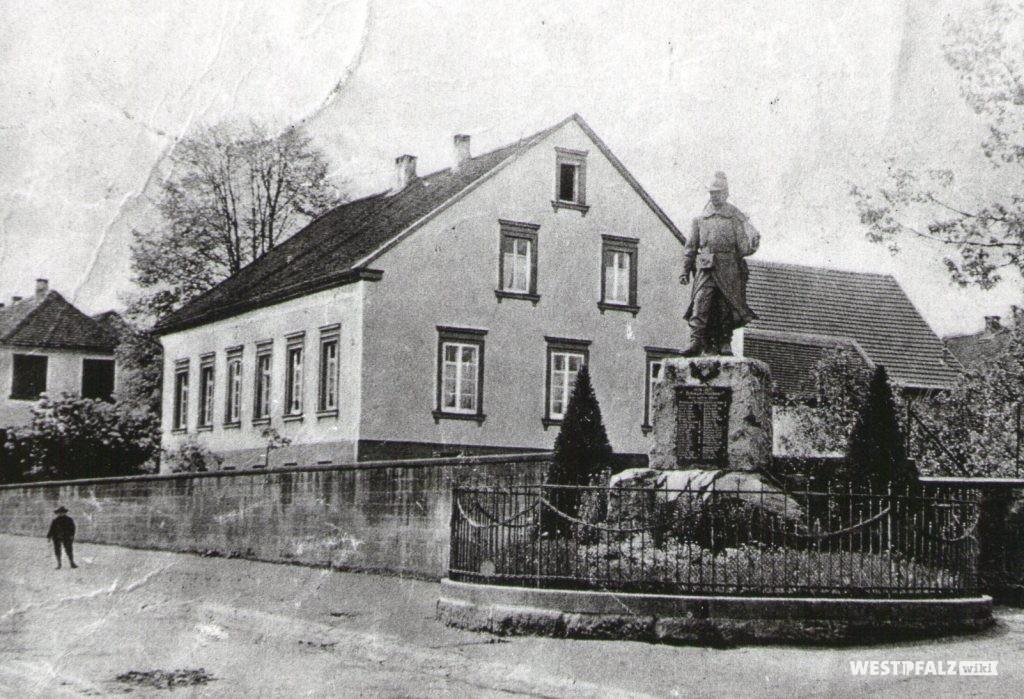Ehemaliges Pfarrhaus. Im Vordergrund ist das Kriegerdenkmal des deutsch-französischen Krieges zu sehen