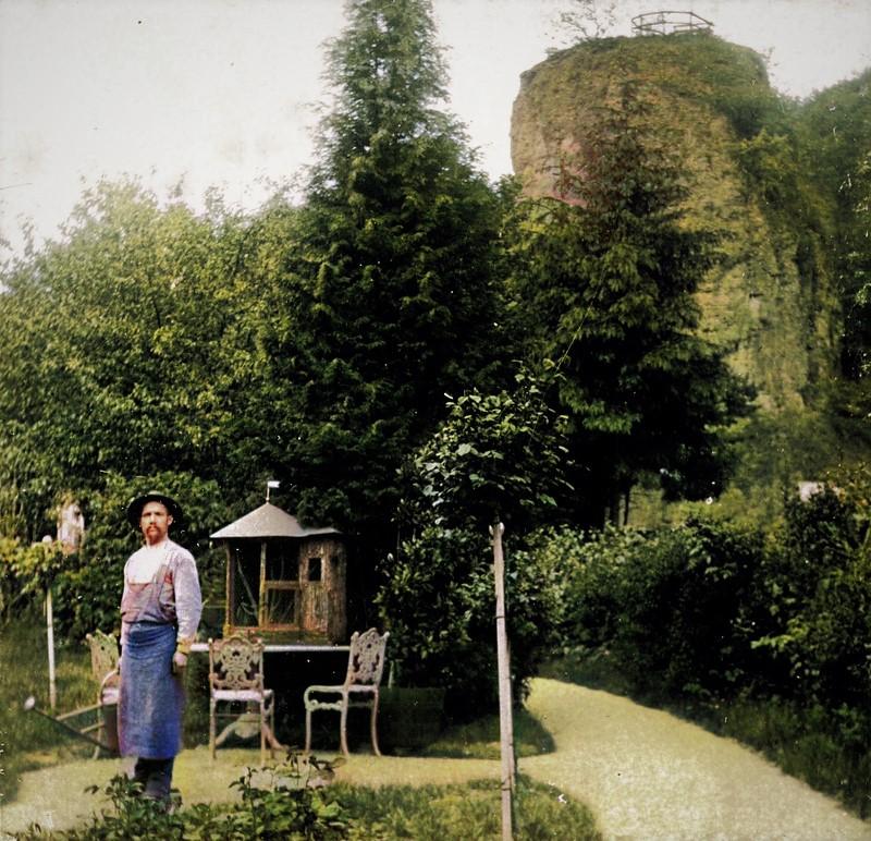 Im Vordergrund ein Gärtner des Herrenhausgartens und im Hintergrund der Aussichtspunkt des Felsengartens